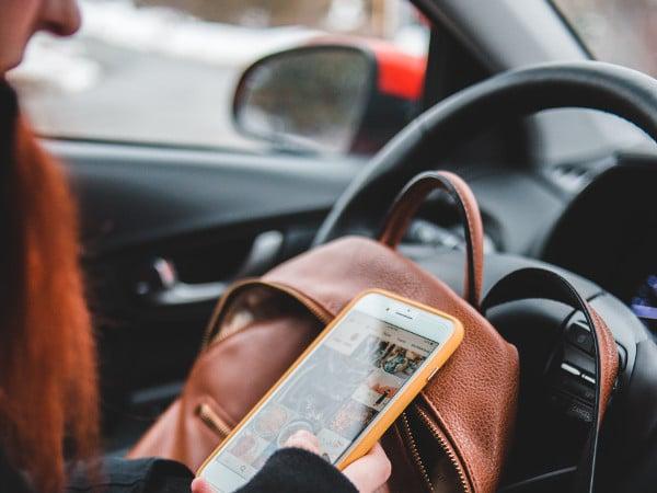 Vrouw stuurt whatsappberichten achter stuur van auto